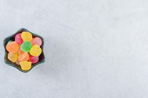 Bol noir de marmelades de gelée colorées sur marbre.