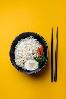 Bol noir de nouilles chinoises cuites rapidement avec des œufs et des légumes baguettes noires près d'elle sur fond jaune copyspace