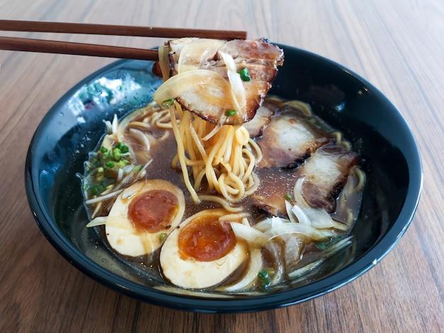 Un bol noir de nouilles shoyu ramen avec du porc et des œufs sur une table en bois