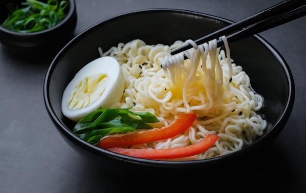 Bol noir avec oeuf de nouilles et légumes et baguettes près sur fond noir