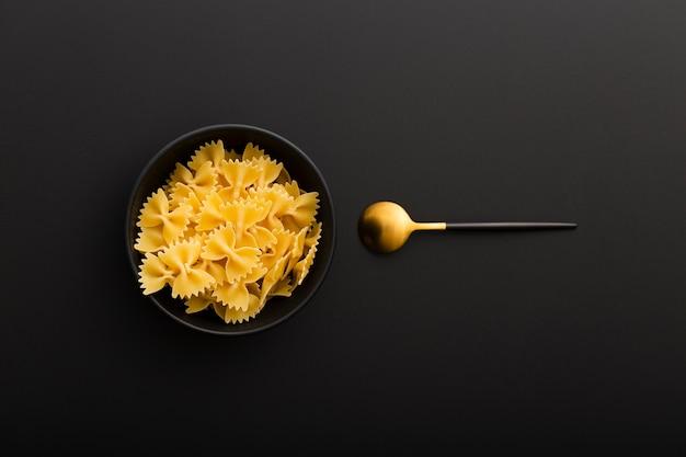Bol noir avec des pâtes et une cuillère sur une table sombre