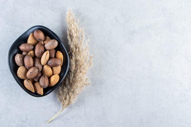 Bol noir plein d'amandes et de noix décortiquées sur pierre.