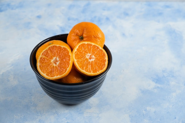 Bol noir plein de mandarines entières ou à moitié coupées
