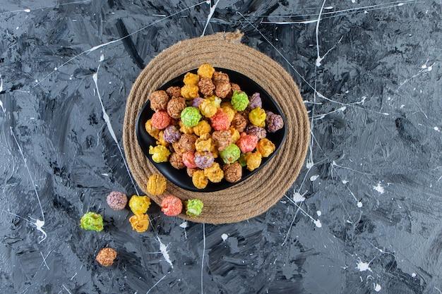 Bol noir de pop-corns savoureux colorés sur une surface en marbre.