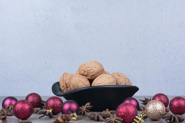 Bol de noix avec clous de girofle et boules de noël.