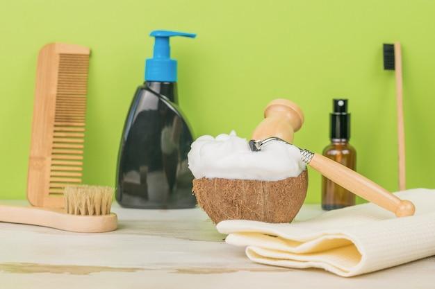 Bol de noix de coco avec mousse, rasoir et accessoires de lavage sur fond vert.