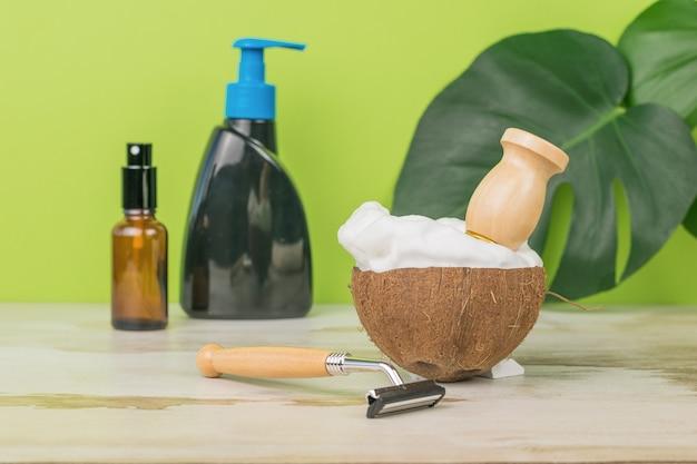 Bol de noix de coco rempli de mousse à raser et d'accessoires de lavage sur fond vert avec des feuilles.