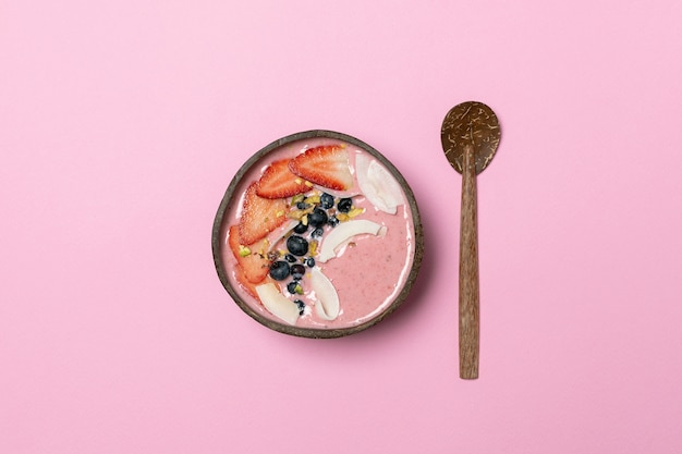 Bol de noix de coco avec smoothie aux fruits, fraises fraîches, bleuets, chips de noix de coco