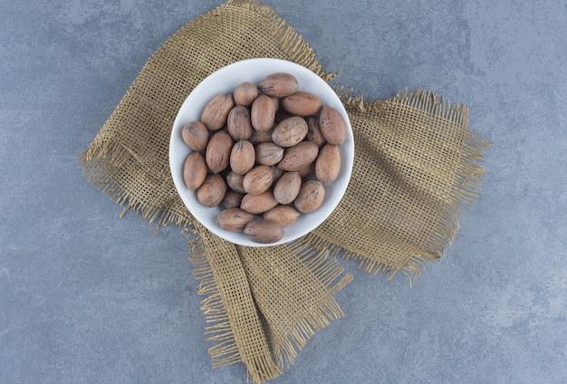 Un bol de noix sur le dessous de plat, sur le fond de marbre.
