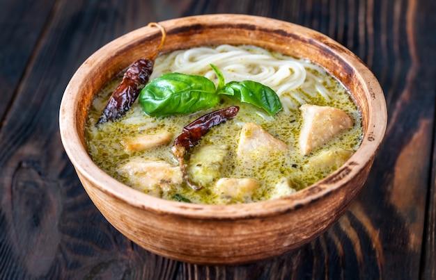 Bol de nouilles au curry vert décoré de basilic frais