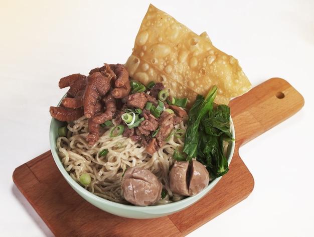 Un bol de nouilles au poulet indonésiennes avec du poulet, des pinces, des boulettes de viande, des feuilles de moutarde et des oignons verts