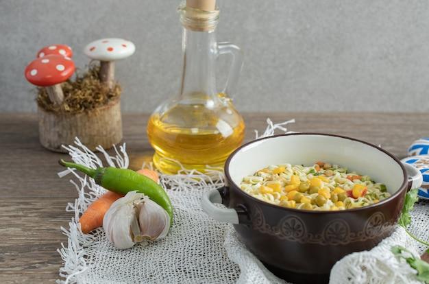 Bol de nouilles, bouteille d'huile et de légumes sur table en bois