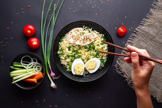 Bol de nouilles ramen avec poulet, légumes et oeuf sur fond noir vue de dessus.