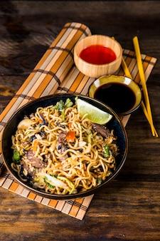 Bol de nouilles udon aux sauces soja et piment rouge sur un napperon contre un bureau en bois
