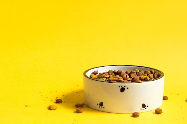 Bol de nourriture pour animaux de compagnie avec des aliments granulés secs sur fond jaune.