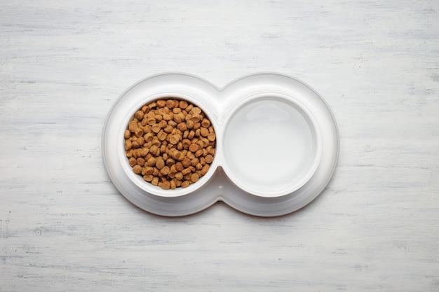 Bol de nourriture pour chat sur fond en bois, vue de dessus