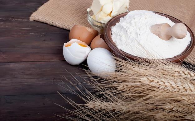 Bol avec des œufs de farine épis de blé et de beurre sur le concept de nourriture et de boissons vintage planche de bois