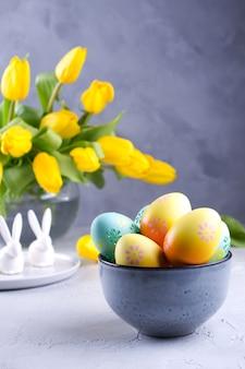 Bol avec des oeufs de pâques colorés; décoration de pâques de printemps sur table grise avec bouquet de fleurs de tulipes jaunes dans un vase en verre; décoration intérieure de pâques