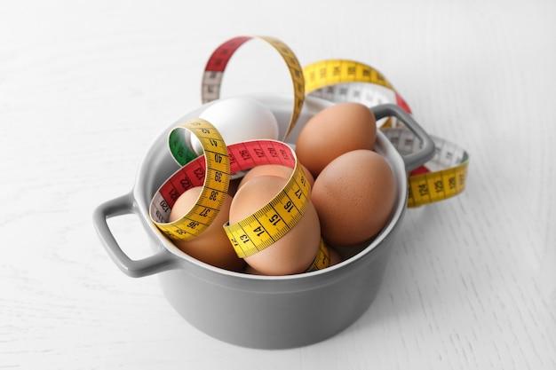 Bol avec des œufs et ruban à mesurer sur la table. concept de nutrition