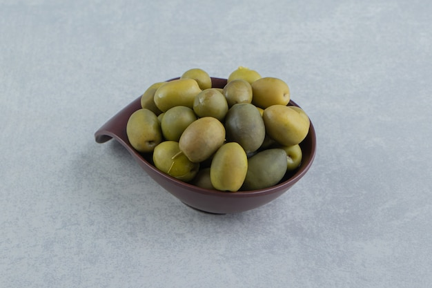 Un bol d'olive crue sur la surface en marbre