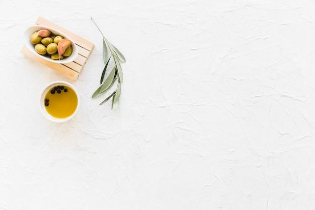 Bol d'olive avec de l'huile de poivre noir et une brindille