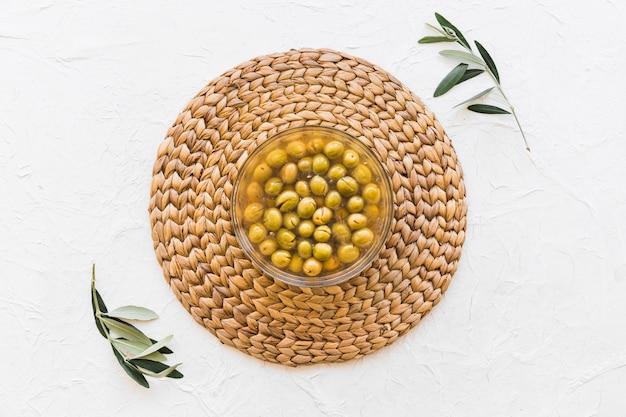 Bol d'olives sur les montagnes russes avec deux brindilles sur le fond blanc