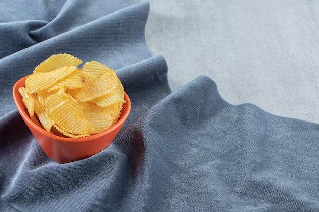 Bol orange de délicieuses chips d'ondulation sur pierre.