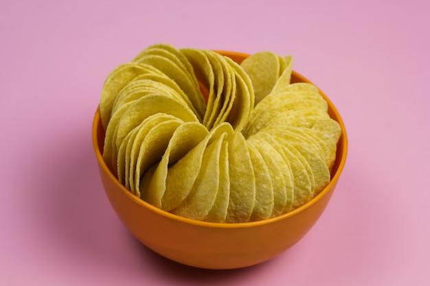 Bol orange plein de pommes pastel rose fond pastel