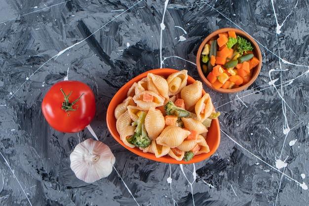 Bol orange de savoureuses pâtes aux coquillages avec salade de légumes sur une surface en marbre.