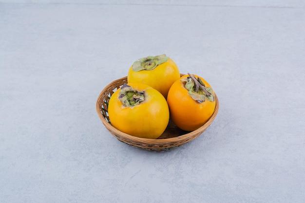 Un bol en osier de trois kakis sur fond blanc. photo de haute qualité
