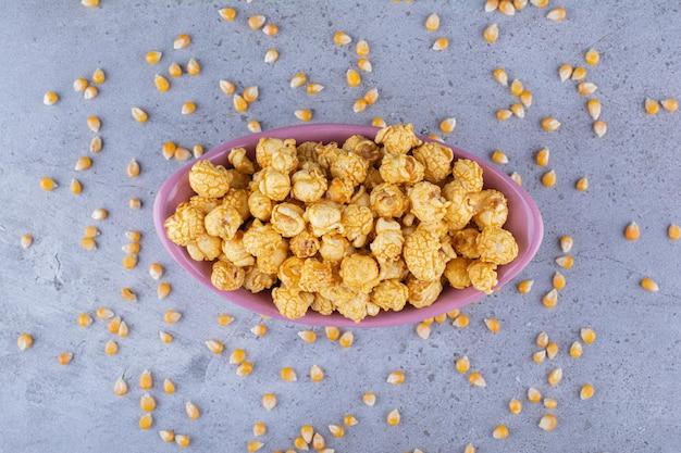 Bol ovale de maïs soufflé au caramel avec des grains de maïs éparpillés sur la surface en marbre