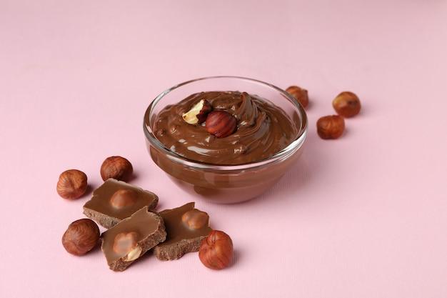 Bol avec pâte de chocolat, noix et chocolat sur fond rose
