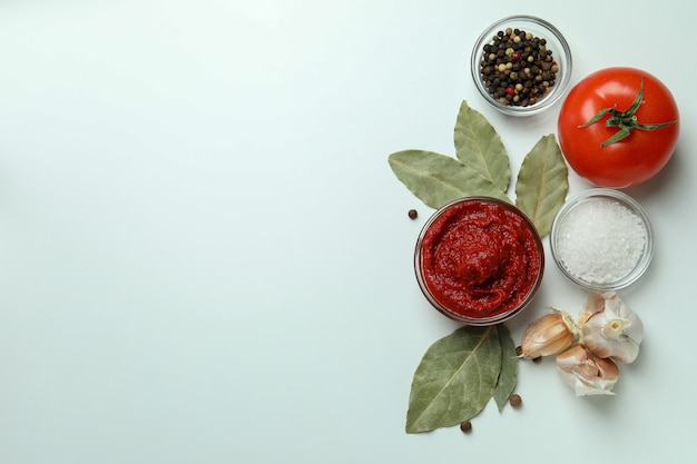 Bol avec de la pâte de tomate sur fond blanc avec des ingrédients