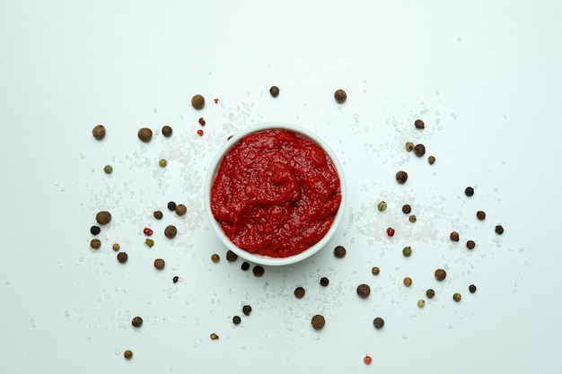 Bol avec pâte de tomate, poivre et sel sur fond blanc