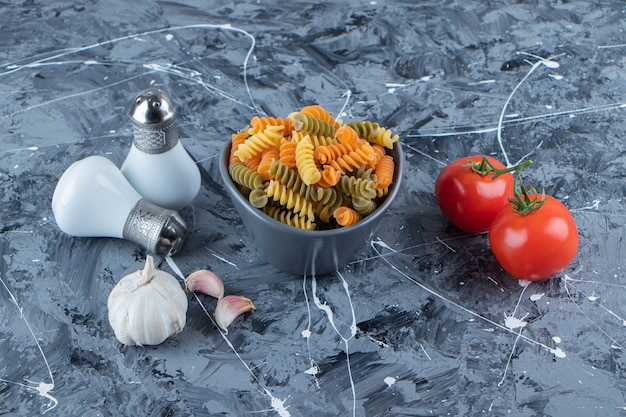Un bol de pâtes crues avec des légumes frais et des épices sur une surface en marbre.
