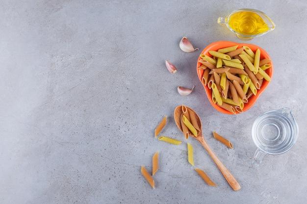 Un bol de pâtes crues multicolores avec de l'huile et une tasse en verre d'eau.