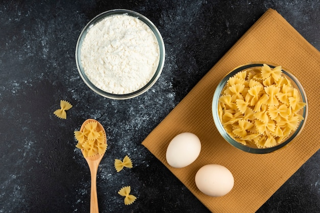 Bol de pâtes crues, œufs et farine sur bleu.
