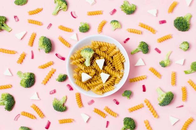 Bol de pâtes fraîches sur la table entouré de légumes