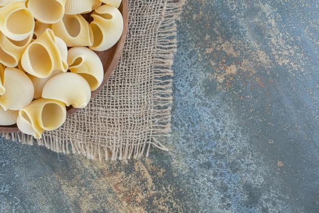 Un bol de pâtes mélangées , sur la surface en marbre.
