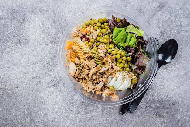 Bol de pâtes santé poulet, pâtes fusilli, mélanger les légumes verts, les pois verts et un bol en plastique.