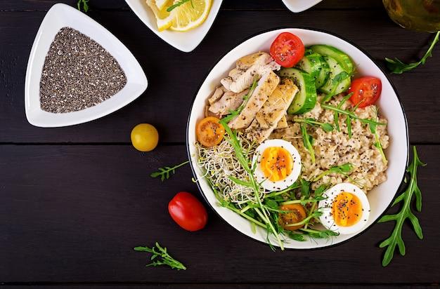 Bol petit-déjeuner avec flocons d'avoine, filet de poulet, tomates, laitue, micro-légumes et œuf à la coque.