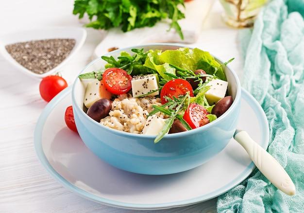 Bol de petit déjeuner avec flocons d'avoine, tomates, fromage, laitue et olives