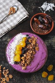 Bol de petit-déjeuner lumineux avec smoothie pourpre proton et granola. smoothie violet proton.