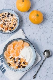 Bol de petit déjeuner vue de dessus avec orange et yaourt
