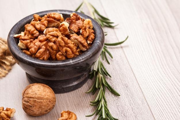 Bol en pierre avec noix pelées et romarin sur un fond en bois. produit protéiné nutritif utile. vue de dessus.