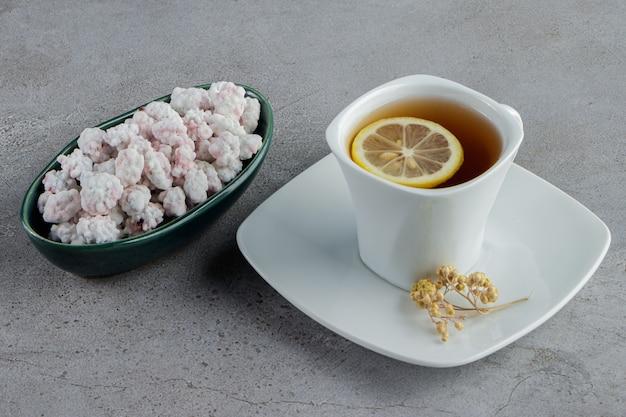 Un bol plein de bonbons blancs sucrés avec une tasse en verre de thé chaud sur une pierre