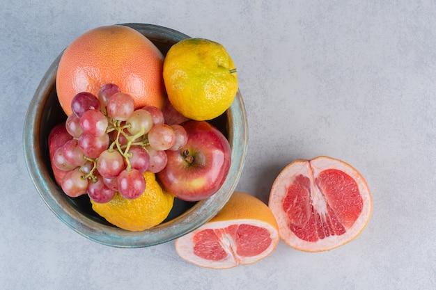 Bol plein de fruits de saison et de pamplemousse coupé à moitié.