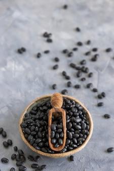 Bol plein de haricots noirs séchés avec une cuillère en bois sur une table grise se bouchent avec un espace de copie. alimentation saine et concept végétarien. ingrédient traditionnel de cousin d'amérique latine
