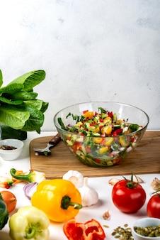 Bol plein de salade de différents légumes écologiques avec des ingrédients et des épices sur la table