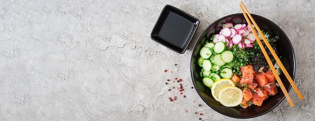 Bol de poisson haché de saumon hawaïen avec riz, radis, concombre, tomate, graines de sésame et algues. bol de bouddha. nourriture diététique. vue de dessus. mise à plat.